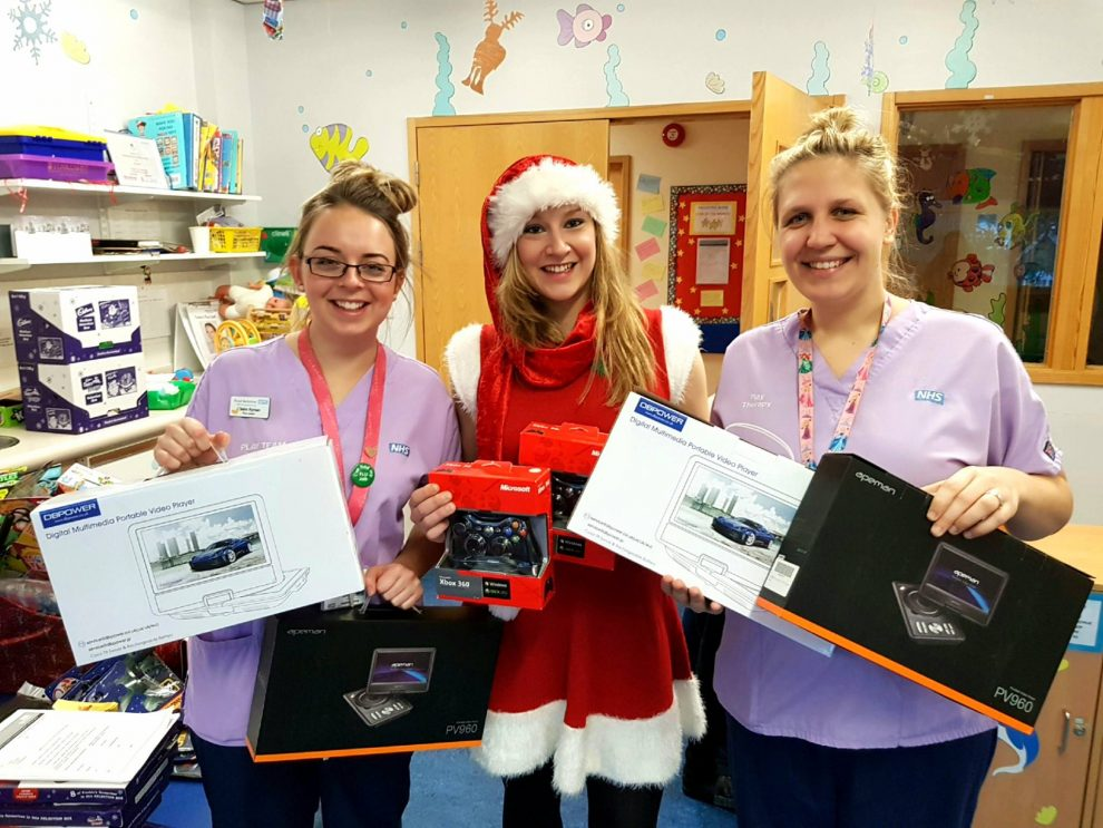 Three ladies holding boxes of electronic good, middle lady dressed as santa